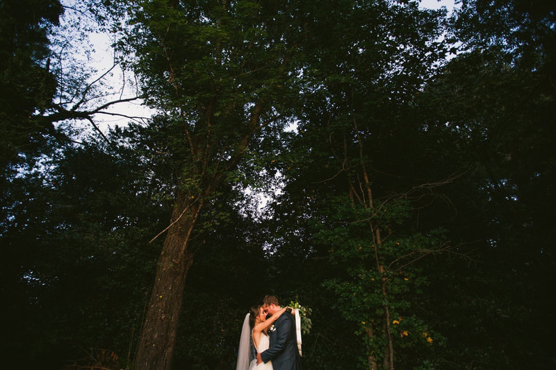 forest wedding with couple dancing around tall trees