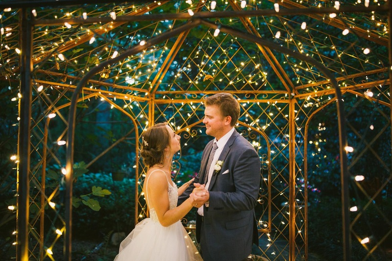 bride and groom's first dance under lit gazebo