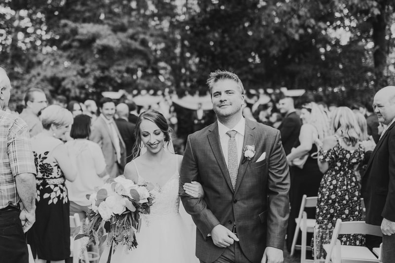black and white photo of newly married couple walking down aisle together