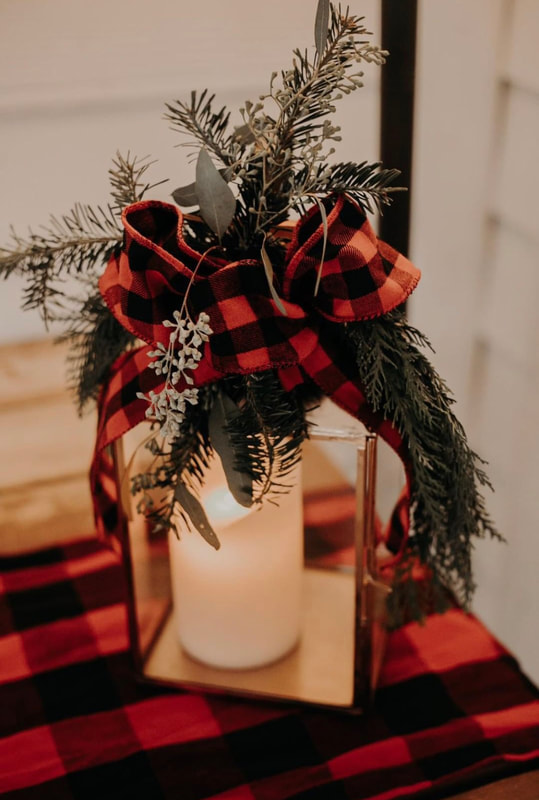 Christmas inspired centerpiece with evergreen leaves, buffalo plaid ribbon, and candle