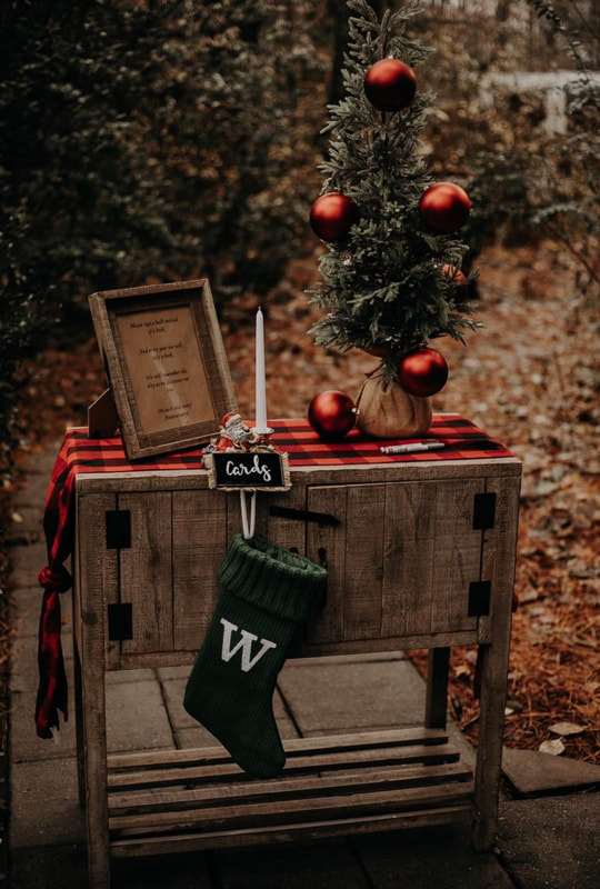 Christmas guest book table with buffalo plaid fabric, green stocking, and mini tree