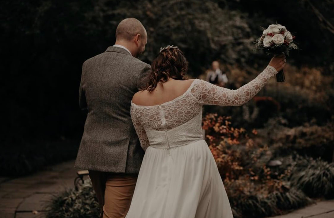 bride holds bouquet in celebration as she walks down aisle with groom