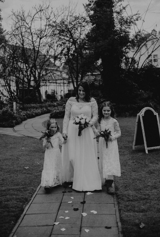 black and white photo of bride with daughters as flower girls