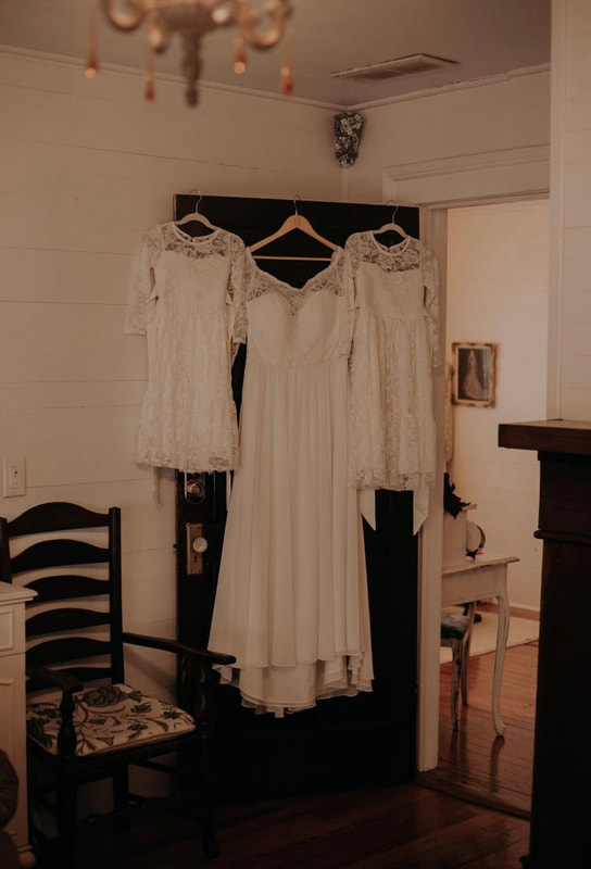 bride's wedding dress hanging with flower girl dresses on farmhouse door