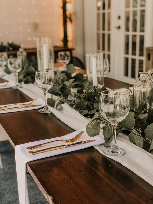 Place settings with white napkin, gold flatware, and wine glasses