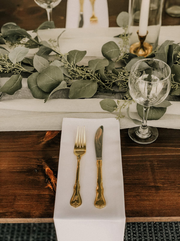 Gold flatware on top of white napkin hanging off farmhouse table with wine glass