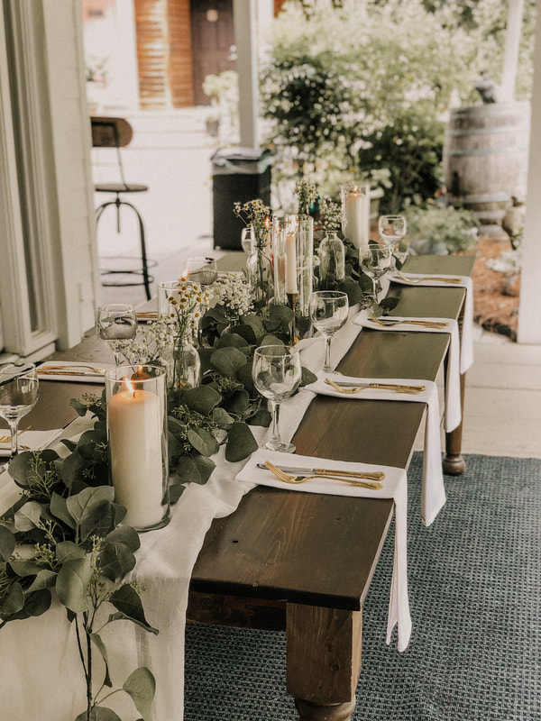 Dark farmhouse table display with candles in glass cylinders