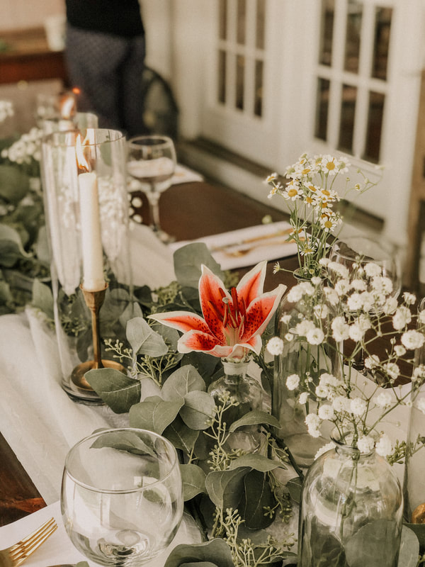 white and greenery tablescape centerpiece with pink flower