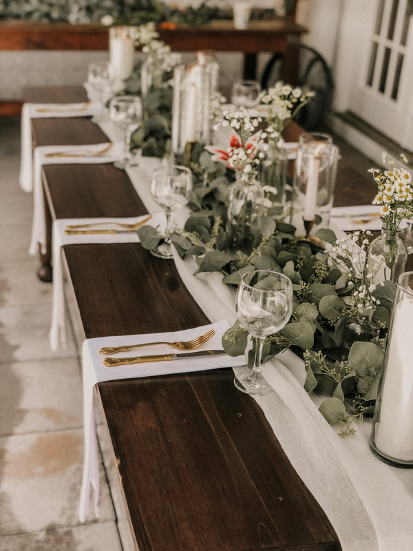 elegant white, gold, and greenery tablescape on dark farm table
