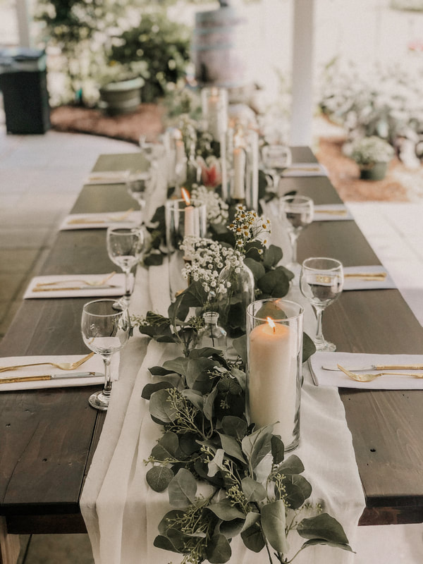 dark farmhouse table with white and greenery elegant tablescape