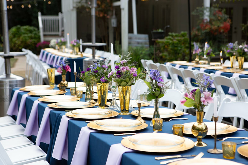 rectangle tables with blue table cloths, lavender napkins and floral arrangements, and gold accents