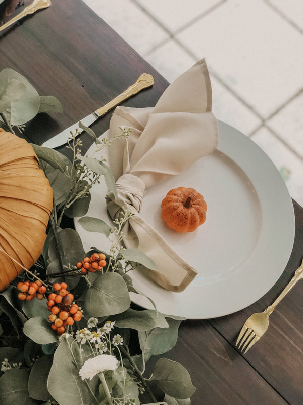 Four Oaks farm table with white ceramic charger, tan napkin in a knot, and a mini pumpkin
