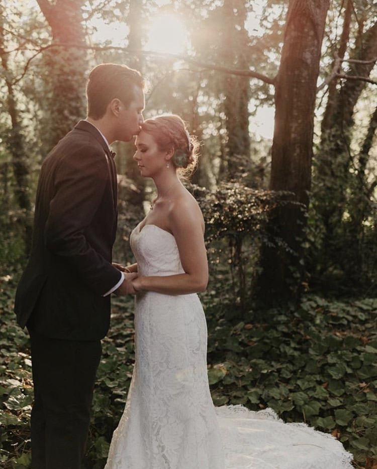 husband kissing wife's forehead in four oaks manor's woods