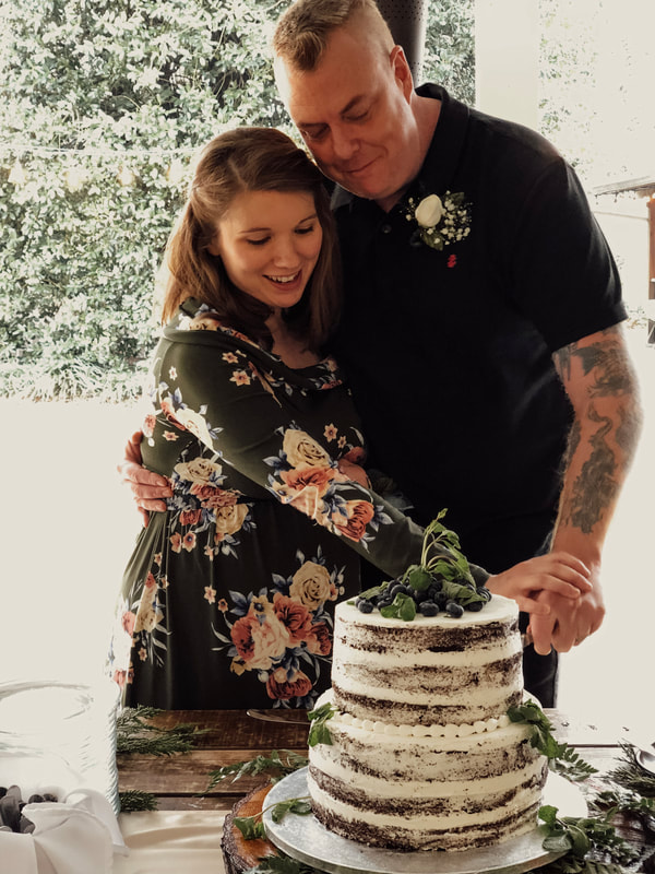 mom and dad to be cutting cake during baby shower