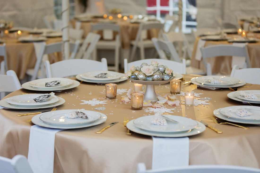 winter themed reception tables with champagne overlay, white place settings, and ornament centerpieces
