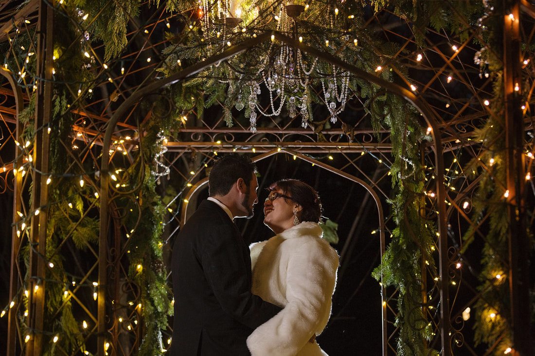 bride and groom's first dance in gazebo decorated with ferns and chandelier
