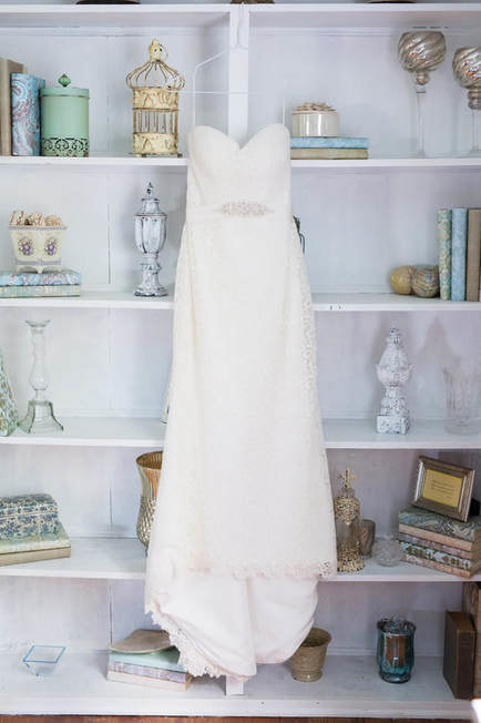 brides lacy dress hanging by vintage shelves