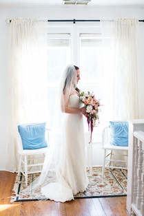 bride holding cascading fall bouquet posing by window with chairs with blue pillows