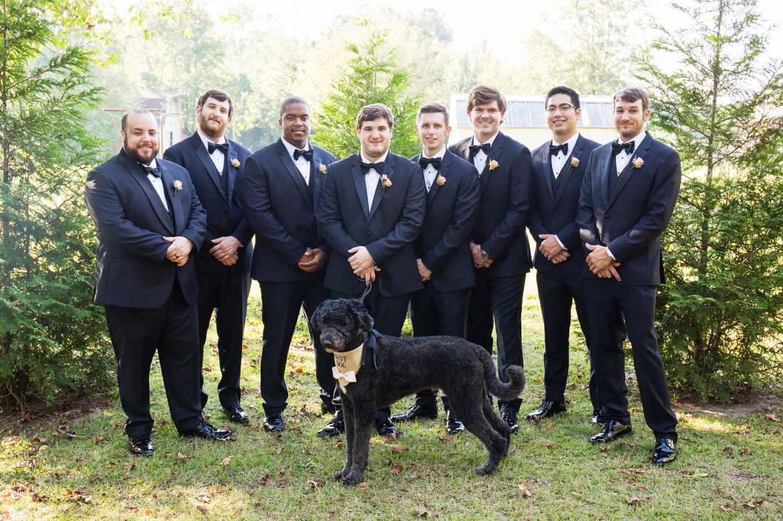 groom and groomsmen posing with black dog