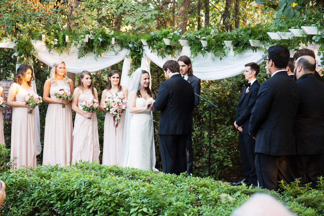 bride and groom exchanging rings during outdoor October wedding ceremony
