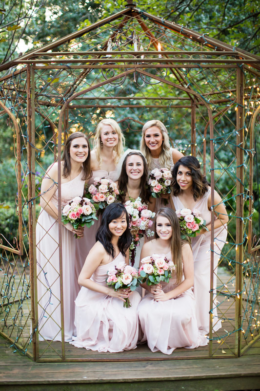 bride and bridesmaids posing in outdoor gazebo with pink and white flower bouquets with eucalytpus
