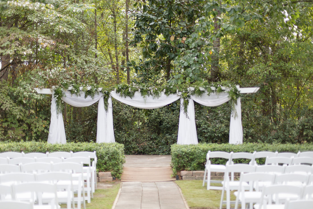arbor decorated with draping white chiffon with greenery running along top and cascading down posts
