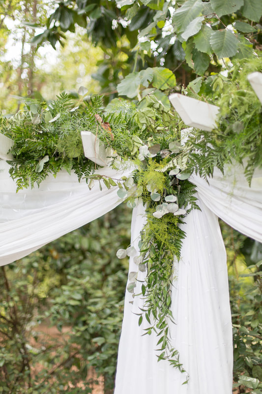 full greenery covering all-white arbor for fall wedding