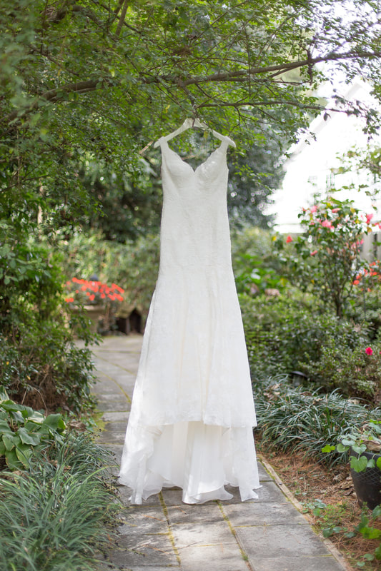 wedding dress with v-shaped neckline hanging from tree in venue gardens