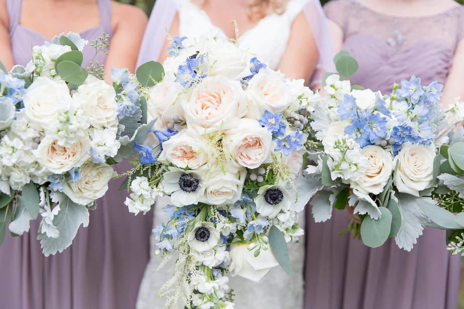 brides cascading bouquet with peach roses and blue and white flowers. Bridesmaids in lavender dresses with white and blue bouquets
