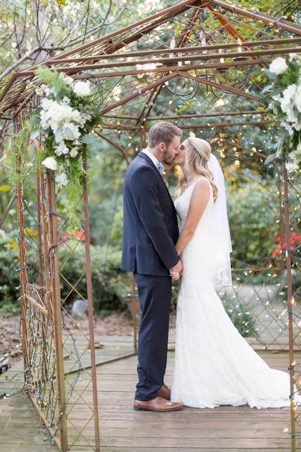 husband and wife kissing under gazebo lights decorated white white flowers and mixed greenery