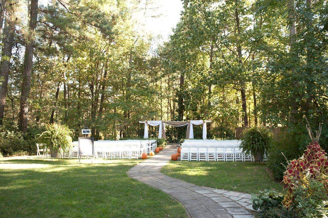 rustic fall ceremony area and arbor with white chiffon and burlap and pumpkin pew markers