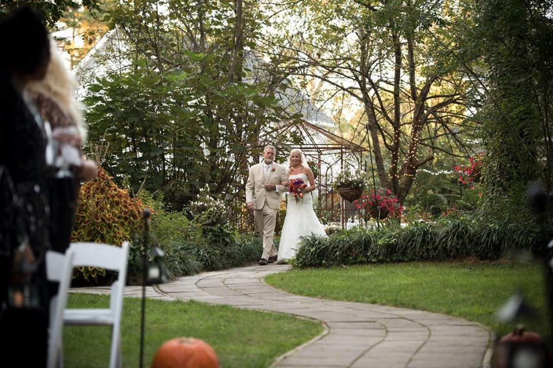 bride walking down aisle with father in tan suit with pumpkins as pew markers
