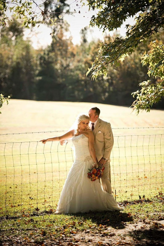 newlyweds posing by large field and leaning against wire fence