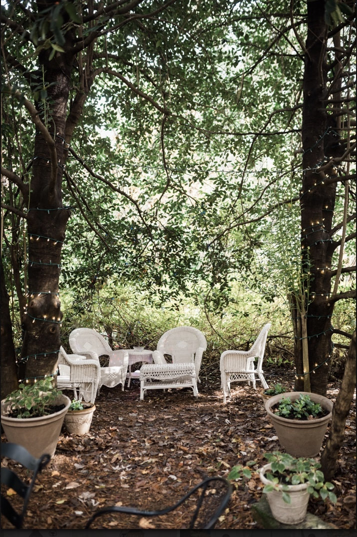 white wicker chairs and tables surrounded by trees. Guest seating area for outdoor wedding