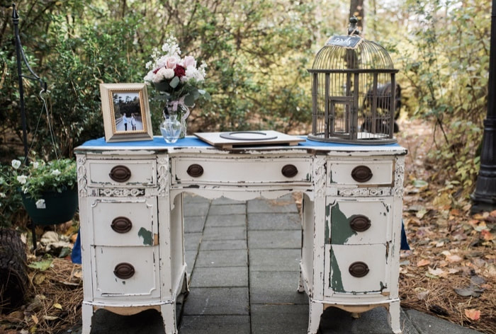 white rustic guestbook table with card cage, engagement photos, blue runner and flowers