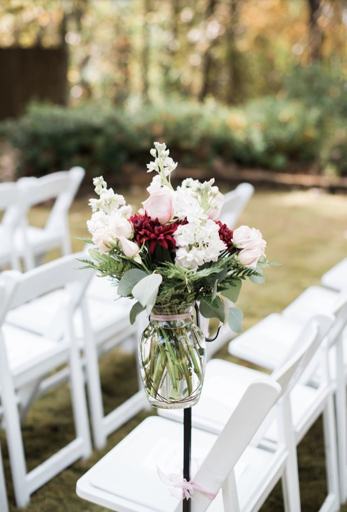 blush, red and white bouquets for pew markers against white chairs