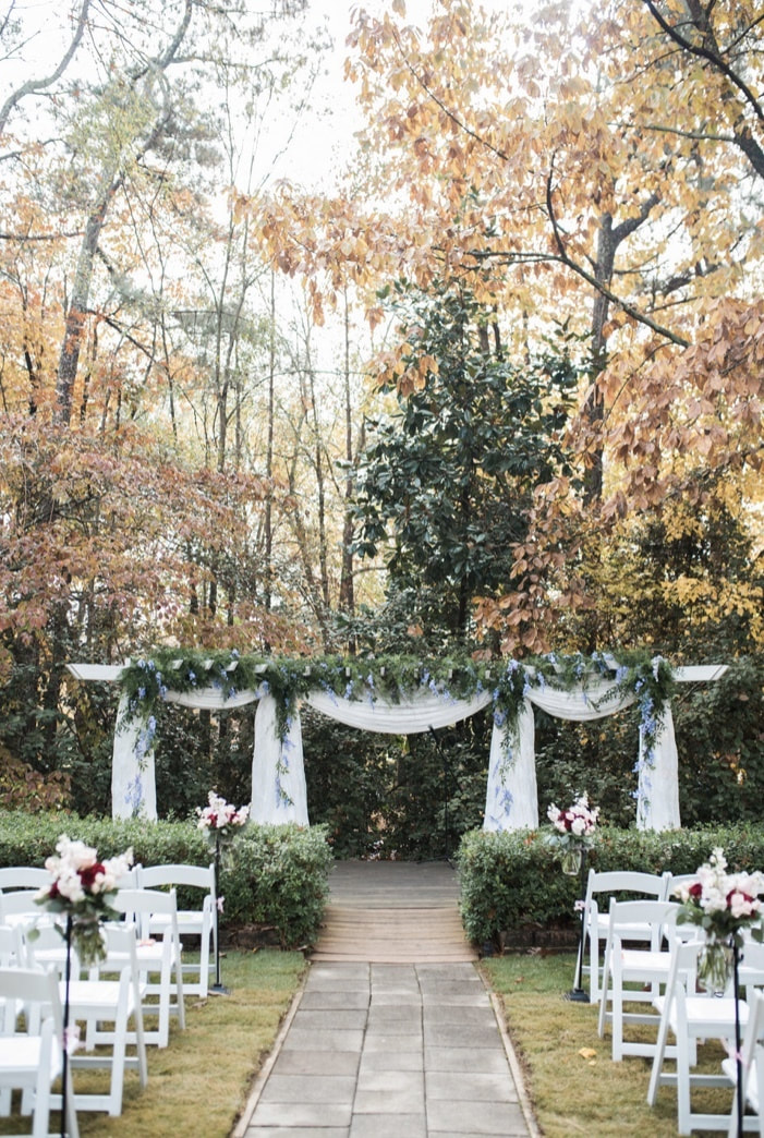 white arbor with chiffon, full greenery, and draping blue flowers