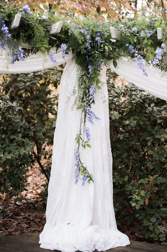 altar decorations with white chiffon and draping greenery and blue flowers