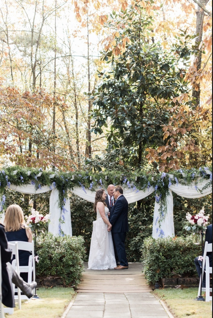 couple and officiant at fall altar with greenery and blue flowers