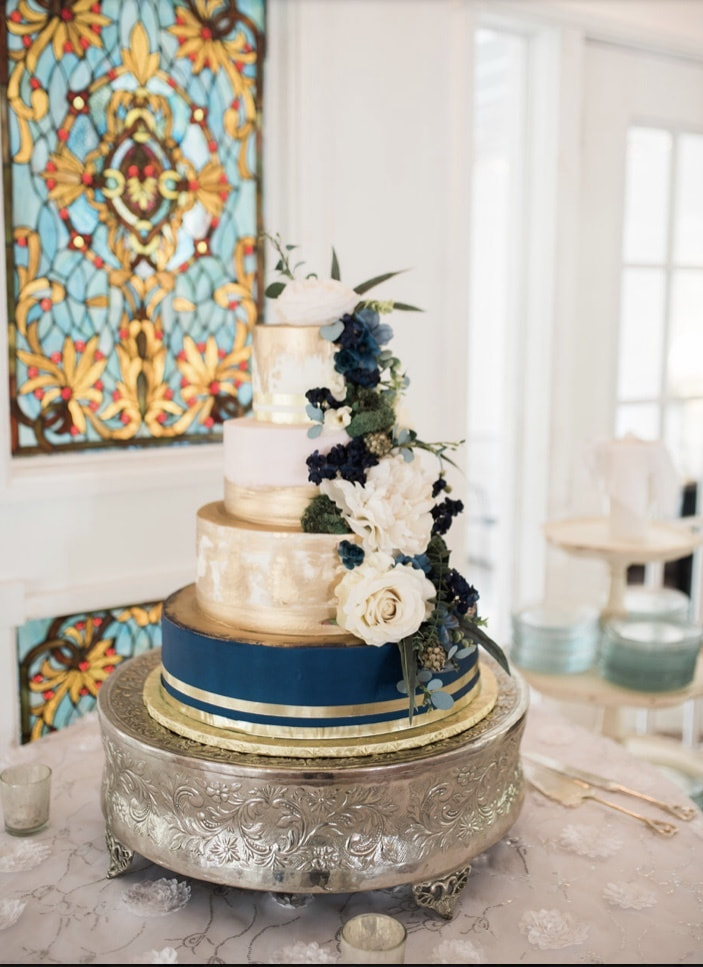 modern wedding cake with navy, gold and champagne accents with white and blue flowers and eucalyptus decorating cake
