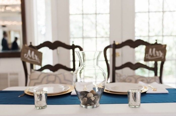 Mr. and Mrs. sweetheart table with silver votives, a vase with pebbles, and mr and mrs wooden signs