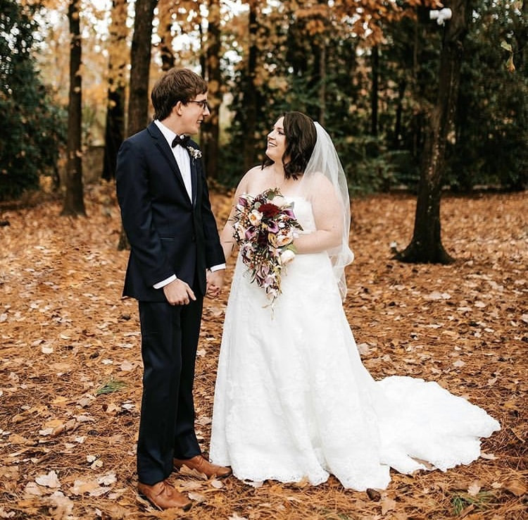Fall wedding with leaves on ground and bride with romantic, cascading bouquet