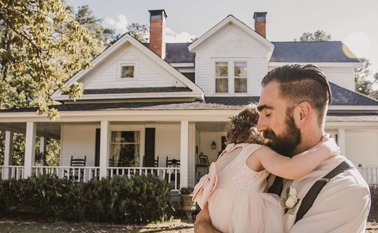 groom hugging young daughter in front of white farmhouse built in 1920s