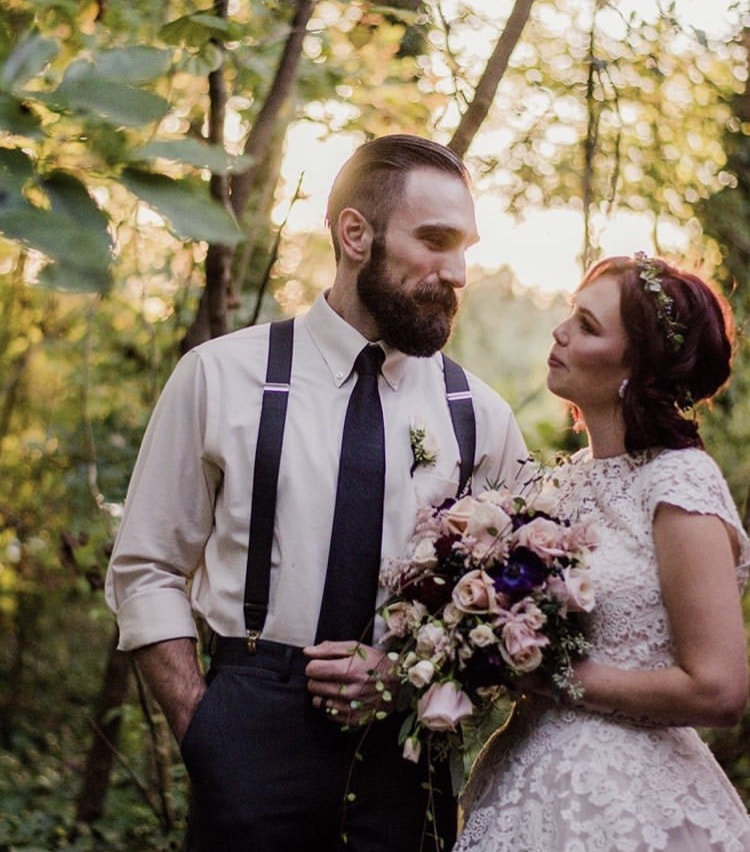 newlyweds posing with modern gothic wedding attire and bouquet at October wedding