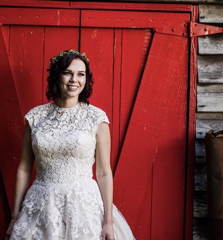 bride in all-lave wedding dress and simple flower crown posing by red barn door