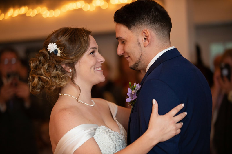 bride in off-shoulder dress with pearl necklace dancing with groom in navy suit with lavender boutonniere