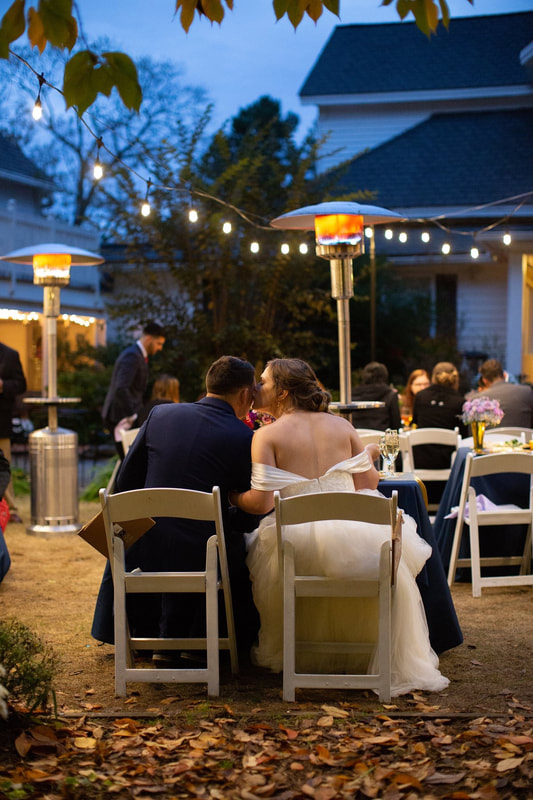 bride and groom at sweetheart table during wedding reception with heat lamps