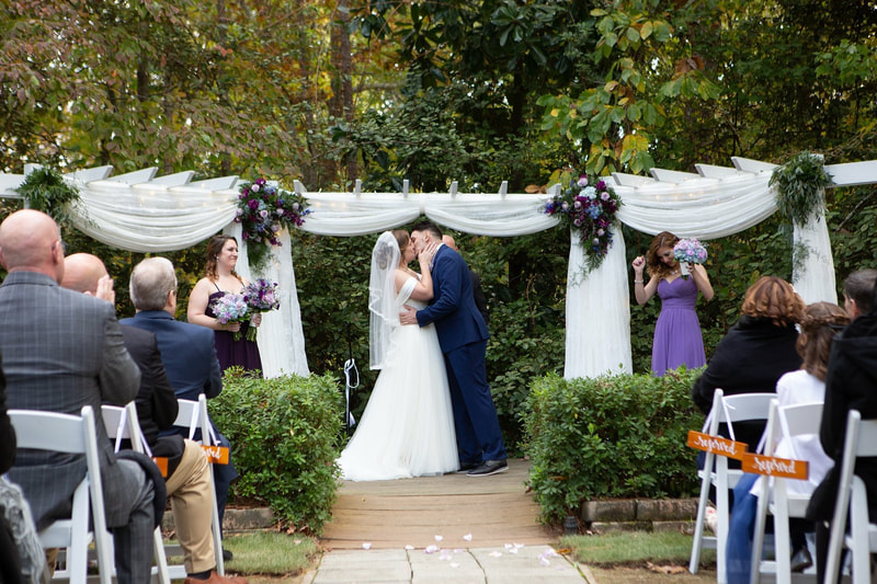 groom in navy suit and bride in classic off-shoulder dress kissing at altar