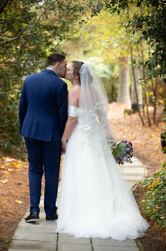 bride and groom holding hands and kissing along stone pathway at outdoor venue in northeast georgia