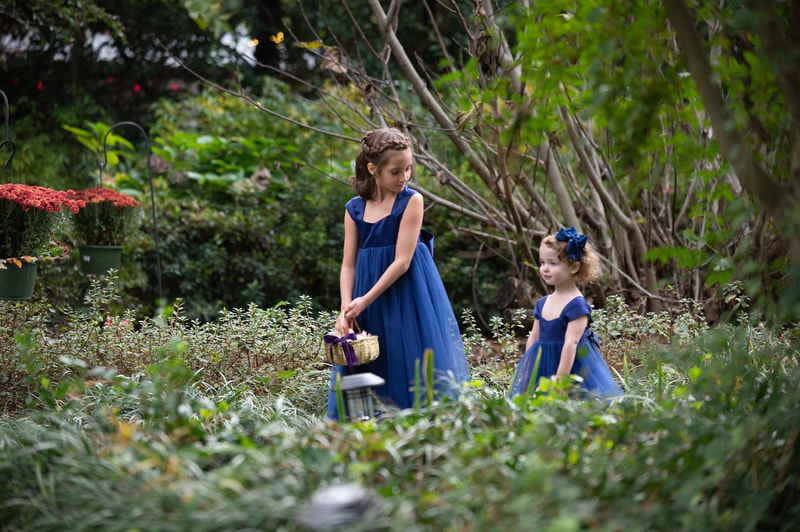 flower girls in ruffled blue dresses during processional